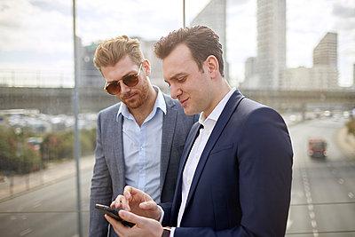 Two businessmen on footbridge texting on smartphone, London, UK - p429m1175142 by Franek Strzeszewski
