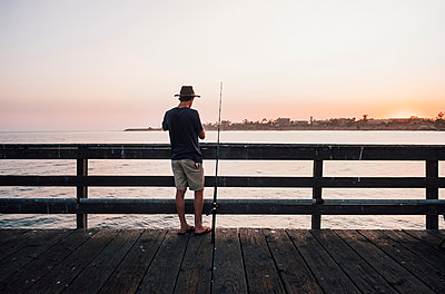 Rear view of man on pier fishing, Goleta, California, United States, North America - p429m1504791 by JFCreatives