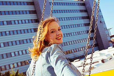 Lächelnde junge Frau im Kettenkarussell - p432m1444534 von mia takahara