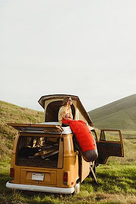 Young male skateboarder looking out from top of vintage recreational vehicle, Exeter, California, USA - p924m1494863 by Peter Amend