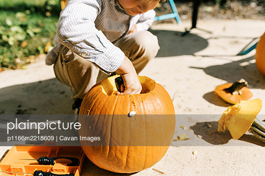 Child carving out pumpkins for halloween on their patio - p1166m2218609 by Cavan Images