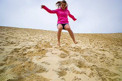 Young girl jumping on the dune of Pyla - p1053m793687 by Joern Rynio