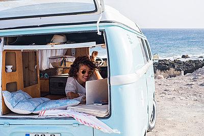 Spain, Tenerife, smiling woman looking at laptop in van - p300m1505910 by Simona Pilolla