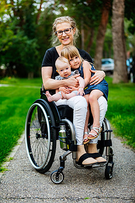 A paraplegic mom carrying her daughters on her lap while using a wheelchair outdoors on a warm summer afternoon and posing for the camera: Edmonton, Alberta, Canada - p442m2156891 by LJM Photo
