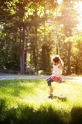 Girl sitting on swing in field - p555m1409495 by Shestock