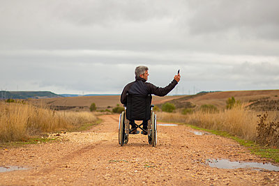 Rear vision of a disabled man in wheelchair in a path taking a selfie - p1166m2146701 by Cavan Images