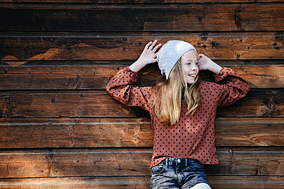 Smiling girl standing in front of a wooden wall outdoors - p300m2144054 von Epiximages