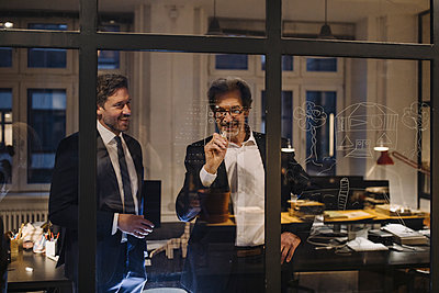 Two businessmen working on drawing on glass pane in office - p300m2154907 by Gustafsson