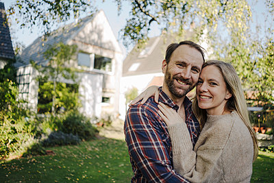 Happy couple embracing in their garden, looking at camera - p300m2167331 by Kniel Synnatzschke