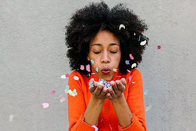 Afro young woman with eyes closed blowing confetti against wall - p300m2257499 by Xavier Lorenzo