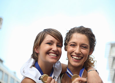 Portrait of two young women (22-25) in running clothing, celebrating with medals, Cape Town, South Africa - p300m2298844 von LOUIS CHRISTIAN