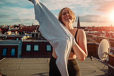 Portrait of smiling woman wearing t-shirt on rooftop against dramatic sky - p426m2233490 by Maskot