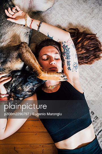 Woman resting with dog on carpet at home - p300m2290797 by Eugenio Marongiu