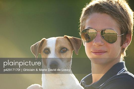 Teenage boy holding dog outdoors - p42917170f by Ghislain & Marie David de Lossy