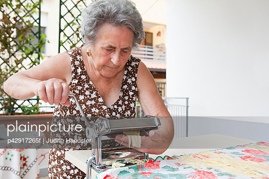 Older woman making pasta with roller - p42917265f by Judith Haeusler
