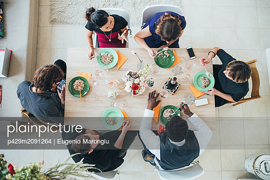 Businessmen and businesswomen celebrating at lunch party in loft office - p429m2091264 by Eugenio Marongiu