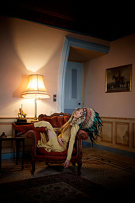 Woman with indian headdress in an armchair, portrait - p1105m2245472 by Virginie Plauchut