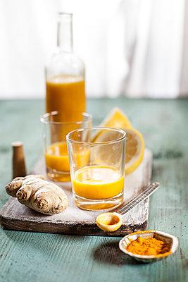 Detox drink, ginger, lemon and orange juice with curcuma and chilli powder - p300m1536159 by Susan Brooks-Dammann