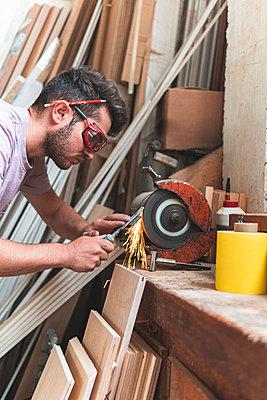 Male craftsperson sharpening chisel on grinder while working in workshop - p300m2252661 by Josu Acosta