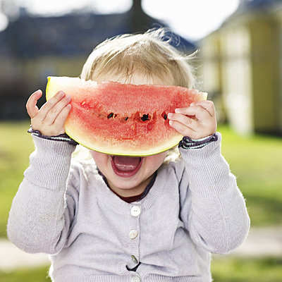 Toddler girl playing with watermelon - p429m746948f by Lisbeth Hjort