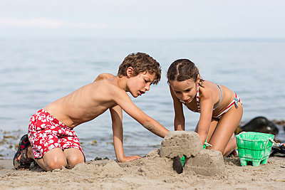 Brother and sister on beach building sandcastle - p429m929469f by Richard Lewisohn
