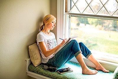 Caucasian woman drawing in windowsill - p555m1409481 by Shestock