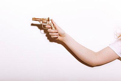 Female arm holding a pistol - p5840824 by ballyscanlon