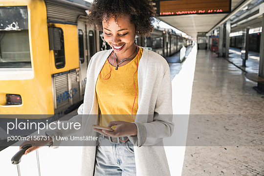 Smiling young woman with earphones and smartphone at platform - p300m2156731 by Uwe Umstätter