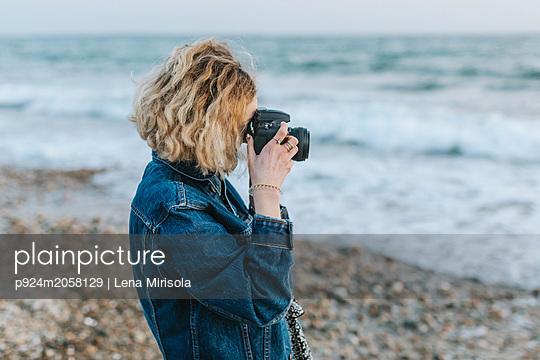 Young woman taking photographs from beach, Menemsha, Martha's Vineyard, Massachusetts, USA - p924m2058129 by Lena Mirisola