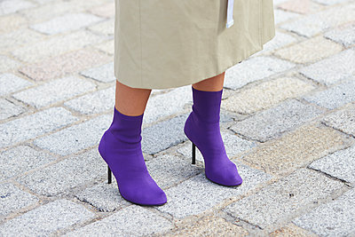 Low section of woman in long beige mac and purple boots - p1407m1545427 by Guerrilla