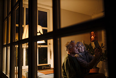 Senior couple using tablet at home at night - p300m2156266 by Gustafsson