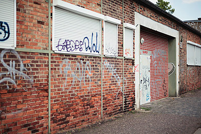 Germany, Saxony, Leipzig, graffiti on facade and closed roller shutters of an old industry building - p300m980637f by Daniel Weisser