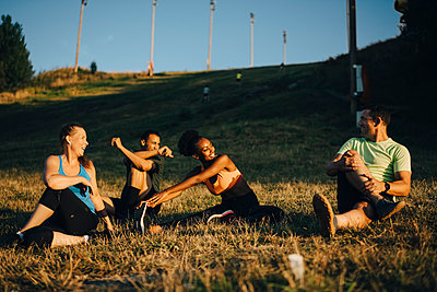 Happy male and female athletes doing stretching exercise on land during sunset - p426m2270568 by Maskot