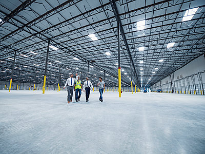 Businessmen walking and talking in empty warehouse - p555m1305141 by Erik Isakson
