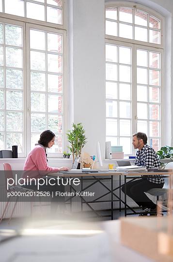 Colleagues working at desk in a loft office - p300m2012526 von Florian Küttler