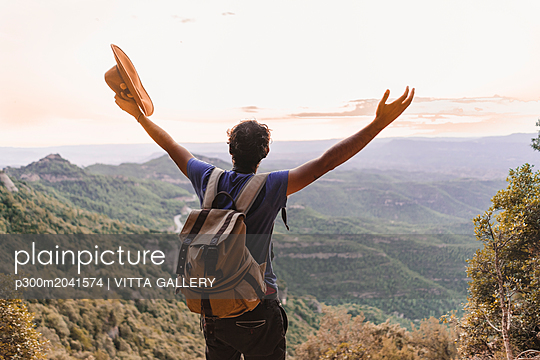 Spain, Barcelona, Montserrat, back view of hiker with backpack looking at view - p300m2041574 von VITTA GALLERY