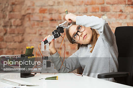 Girl doing scientific experiment on robotic arm at table - p300m2273998 by Studio 27