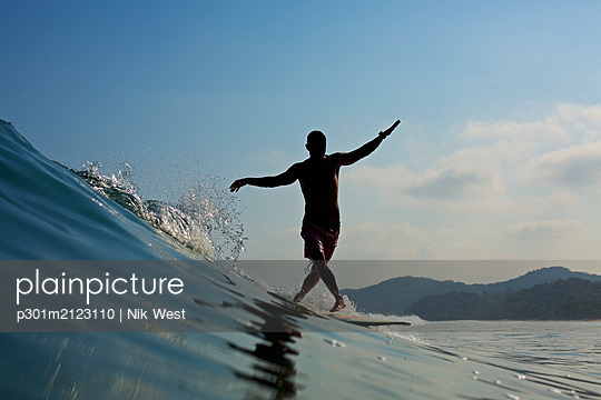 Male surfer balancing on surfboard, riding ocean wave - p301m2123110 by Nik West