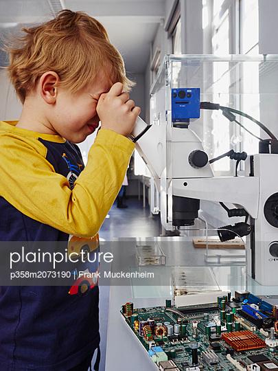 Junge schaut durch ein Mikroskop - p358m2073190 von Frank Muckenheim