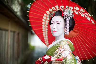 A woman dressed in the traditional geisha style, wearing a kimono and obi, with an elaborate hairstyle and floral hair clips, with white face makeup with bright red lips and dark eyes holding a red paper parasol.  - p1100m1185724 by Mint Images