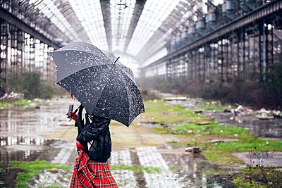 Woman carrying umbrella walking on field during snowfall - p1166m1154166 by Cavan Images