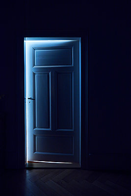 Room door of a old apartment through a beam of light shines - p1312m2175165 by Axel Killian