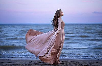 Young woman in dress on beach - p1427m2067276 by Valeriya Tikhonova