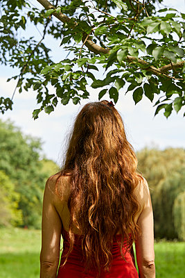 back of long haired redhead woman in nature - p1540m2291469 by Marie Tercafs