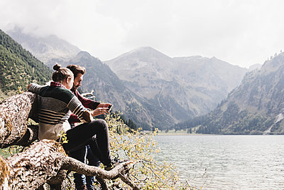 Austria, Tyrol, Alps, couple relaxing on tree trunk at mountain lake using cell phone - p300m1505329 by Uwe Umstätter