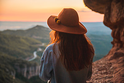 Rear view of woman on a hiking trip looking at view at sunset - p300m2041604 von VITTA GALLERY