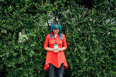 Young woman with dyed blue hair standing in front of a hedge with beverage - p300m2062862 by Vasily Pindyurin
