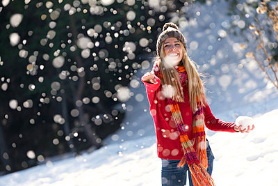 Young blond woman throwing with snow in winter - p300m2114655 by Josep Suria