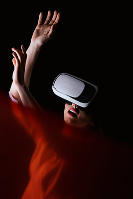 Young woman using VR glasses over black background - p300m2199224 by DREAMSTOCK1982
