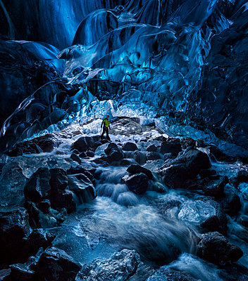 Haukur exploring an ethereal ice cave with a waterfall running through, Iceland - p343m1443996 by Johnathan Ampersand Esper
